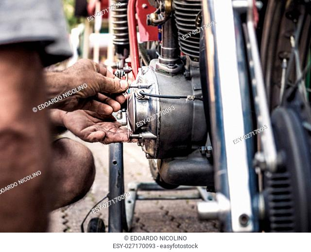 Mechanic with dirty hands fixing a screw on a old bike engine, intentional blur and vivid colors