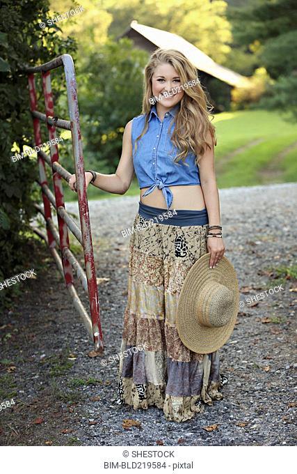 Teenage girl holding straw hat at rural gate
