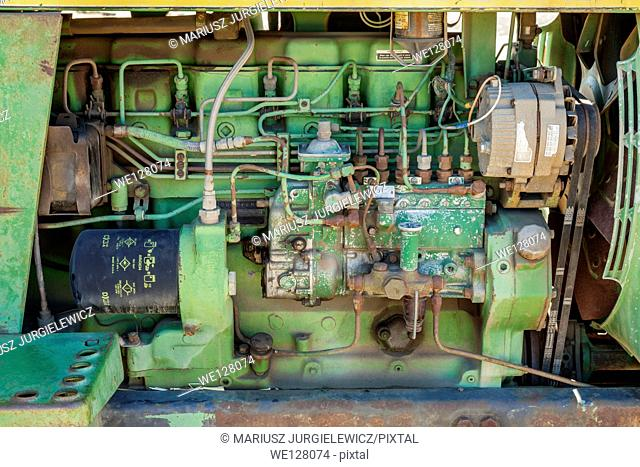 Rusty old tractor engine with various cables