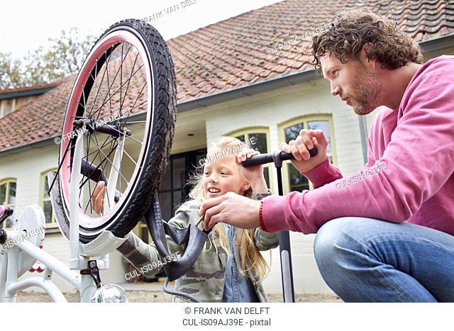 Father and daughter mending bike