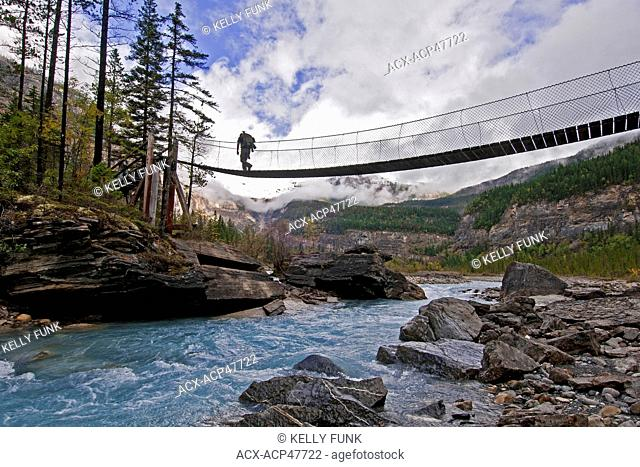 A hiker makes his way across the Robson river just below White Falls at Mt. Robson Provincial park, in the Northern tip of the Thompson Okanagan region of...