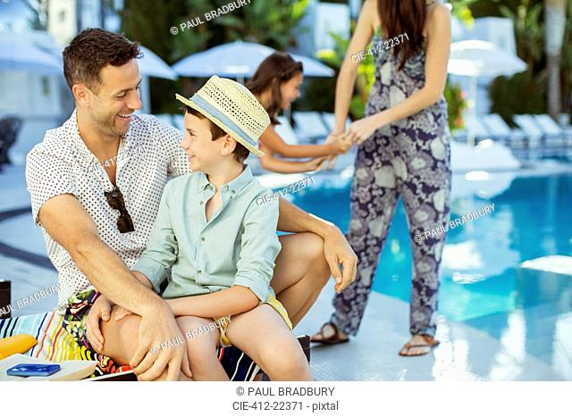 Family with two children enjoying themselves by swimming pool