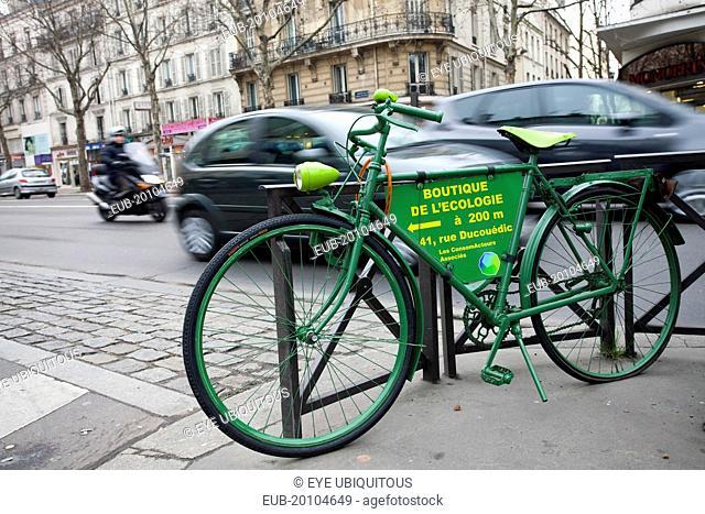 Denfert Rochereau Green bicycle padlocked against railings advertising Boutique de LEcologie