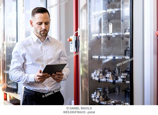Businessman using tablet at a machine in modern factory