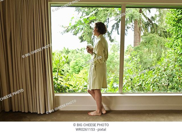 Woman drinking coffee and looking out window in the morning