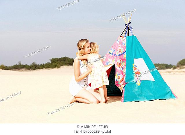 Mother hugging daughter (2-3) on beach
