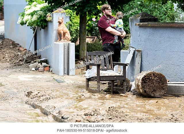 dpatop - 30 May 2018, Germany, Bad Gandersheim: A man standing on his driveway with his son. The floods which occured after heavy rain on Tuesday evening in the...