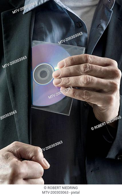 Businessman stealing compact disk, Bavaria, Germany