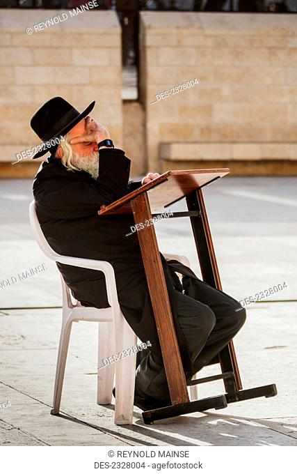 Side view of man with Wailing Wall in background; Jerusalem, Israel