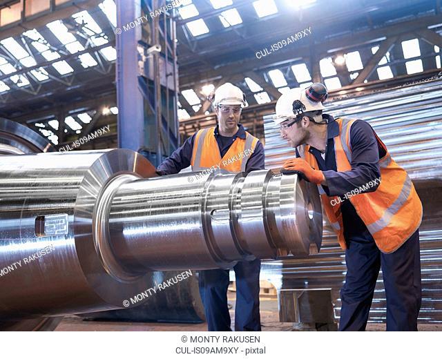 Engineers checking steel part in engineering factory