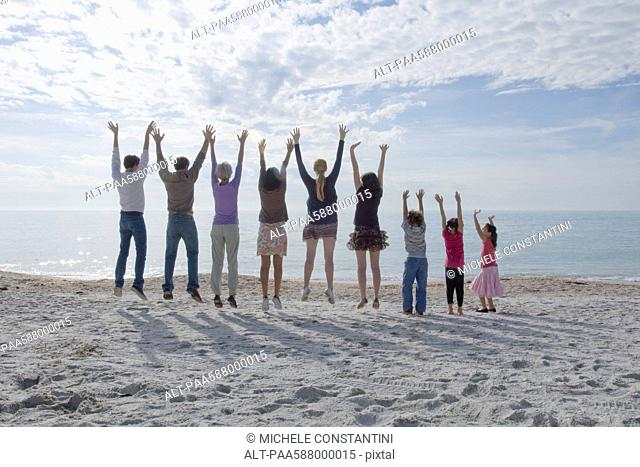Group of people jumping at the beach, arms raised