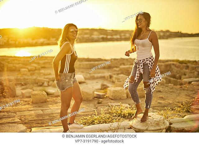 two women at seaside at ancient ruins, friends, hanging out, together, in Chersonissos, Crete, Greece
