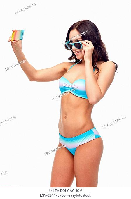 people, technology, summer and beach concept - happy young woman in bikini swimsuit and sunglasses taking selfie with smatphone