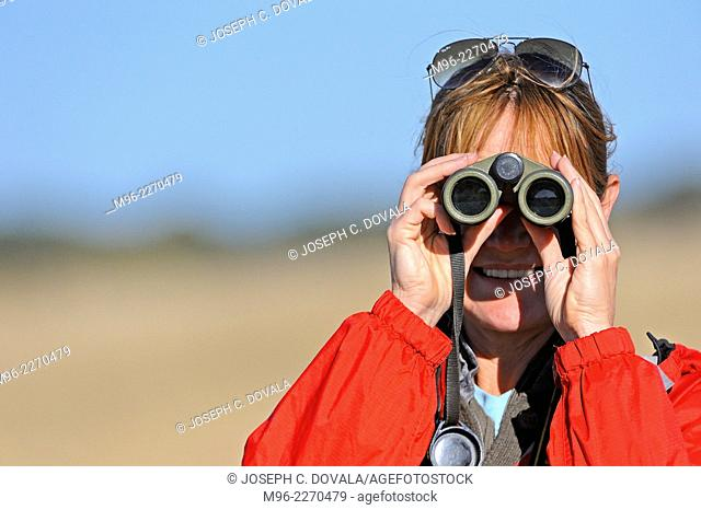 Woman vieing through binoculars, Hwange, Zimbabwe, Africa