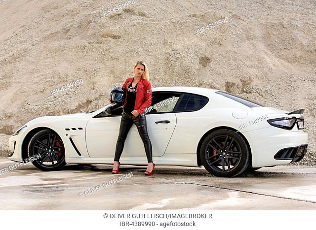 Young woman with long blond hair poses with white Maserati Gran Turismo MC Stradale