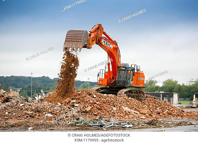A digger working on the demolition of industrial an site