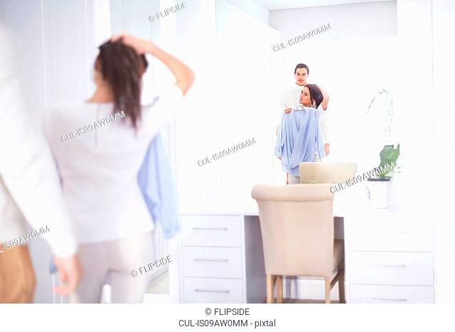 Young woman and boyfriend getting ready in bedroom mirror