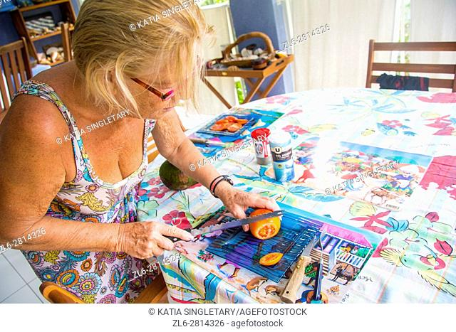 Older senior caucasian retired woman cooking lunch in her house in the Caribbean. She is cutting and slicing a tomato on a blue plate