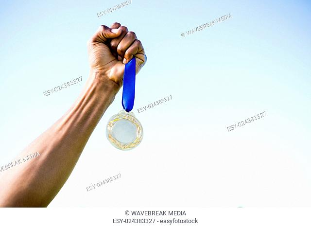 Athletes hand holding gold medal after victory