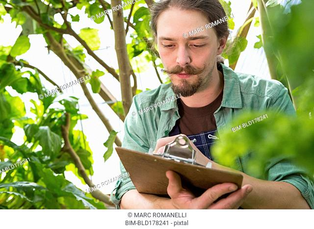 Caucasian gardener writing on clipboard in greenhouse