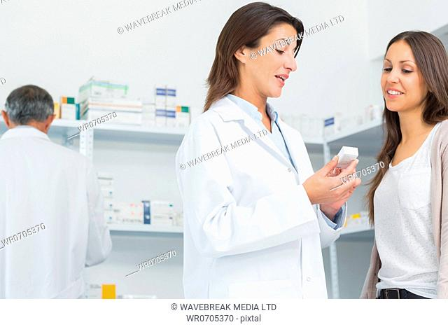 Pharmacist talking to a customer while holding pills in a hospital