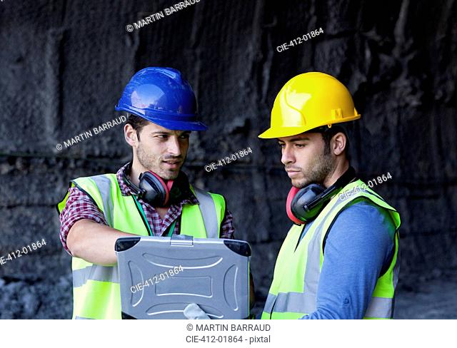 Workers using laptop in tunnel
