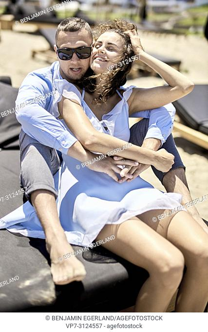 couple sitting on sunbeds, vacations, summer, love