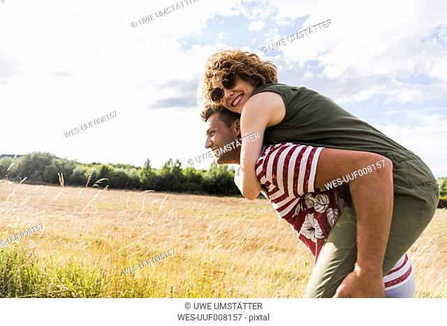 Happy young man carrying girlfriend piggyback in the nature