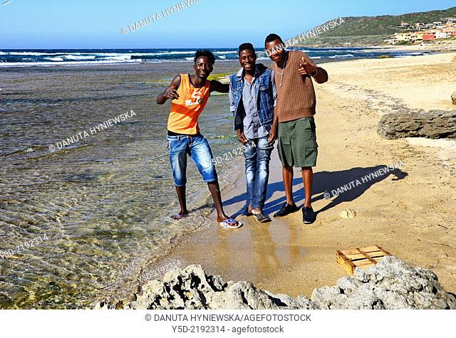 Three young Nigerian men from camp for refugees in Lu Bagnu, Sardinia, Italy