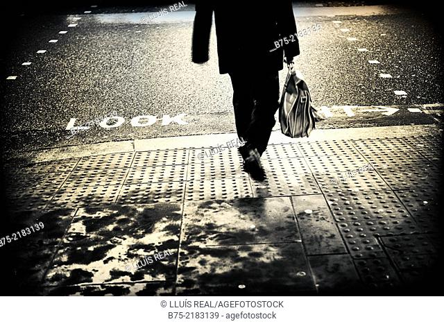 Legs of unrecognizable businessman with portfolio walking down the street with the written text on asphalt look right, in the city of London, England, UK