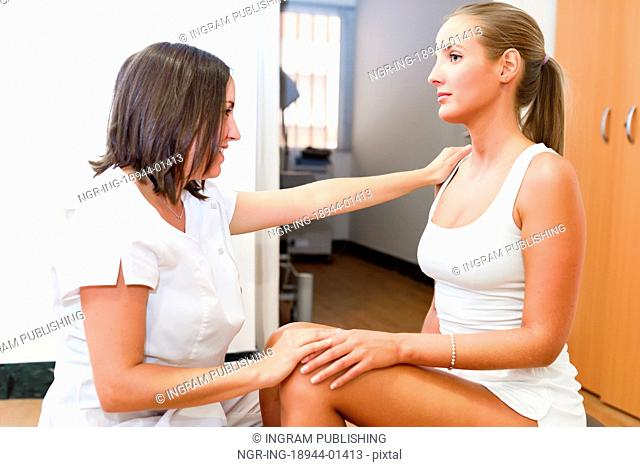 Female physiotherapist inspecting her patient. Medical check to a blonde girl in a physiotherapy center