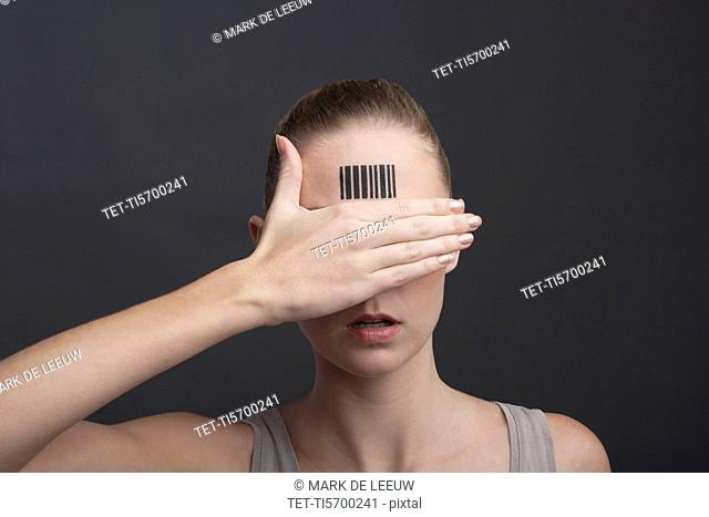 Studio portrait of woman with bar code on forehead