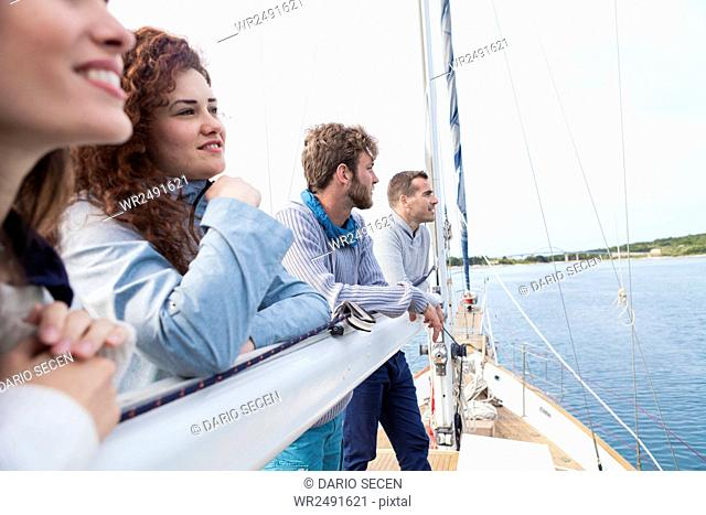 Group of friends leaning against boom of sailboat