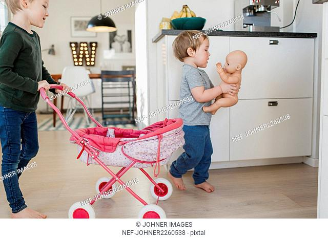 Boys playing with doll pram