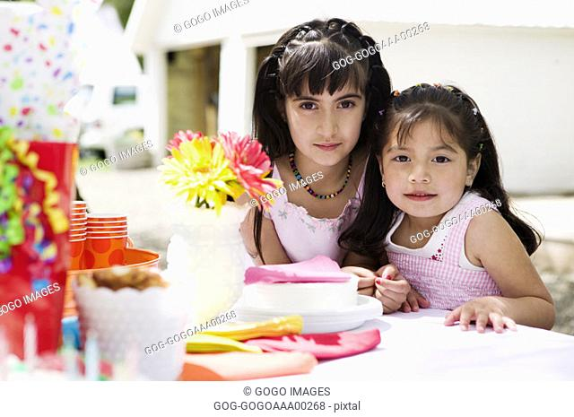 Two girls 4-7 by table, portrait