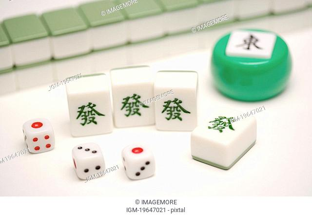 Mah-jongg tiles and dice on table