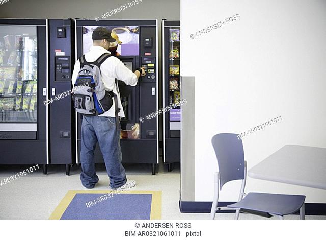 Male student using vending machine