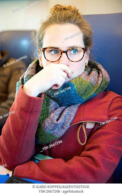 Utrecht, Netherlands. Young brunette woman commuting by intercitytrain to her hometown Tilburg