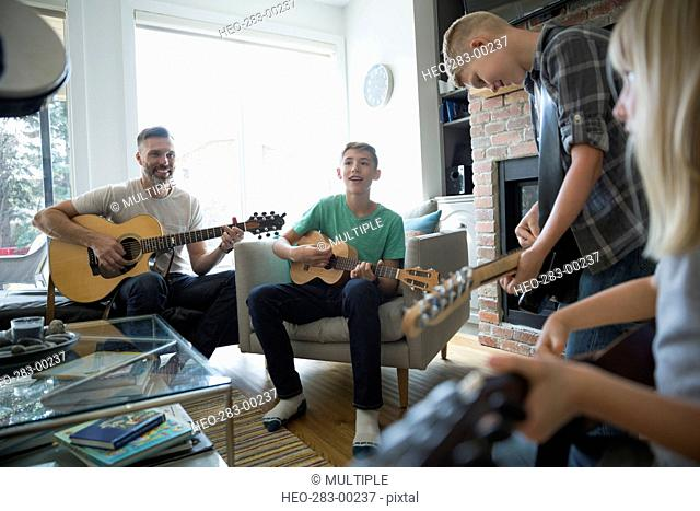 Family playing guitars in living room