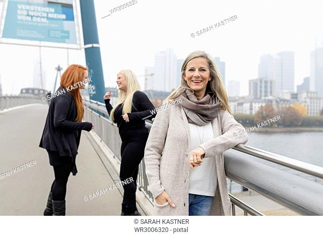 Middle-aged woman standing with two young women on a bridge