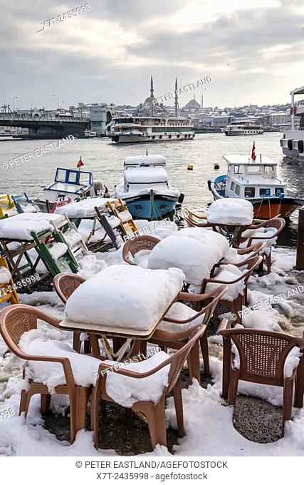 Snow covered cafe chairs on Karakoy waterfront, looking across the Golden Horn toward the Yeni mosque at Eminonu and the Istanbul skyline
