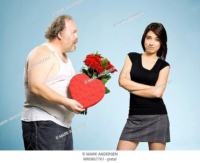 Disheveled man with heart box and red roses with disinterested woman