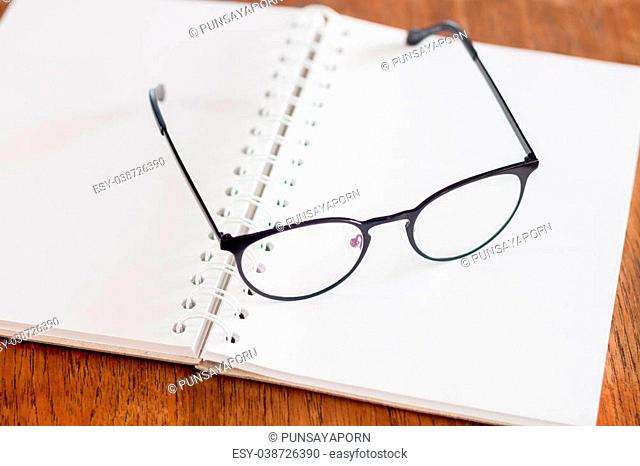 Eyeglasses on opened spiral notebook , stock photo