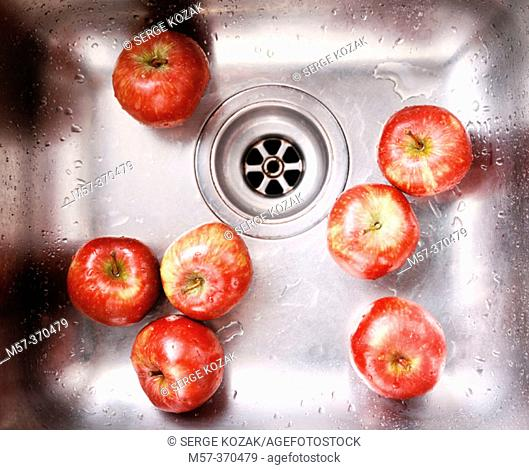 Metal sink with washed red apples