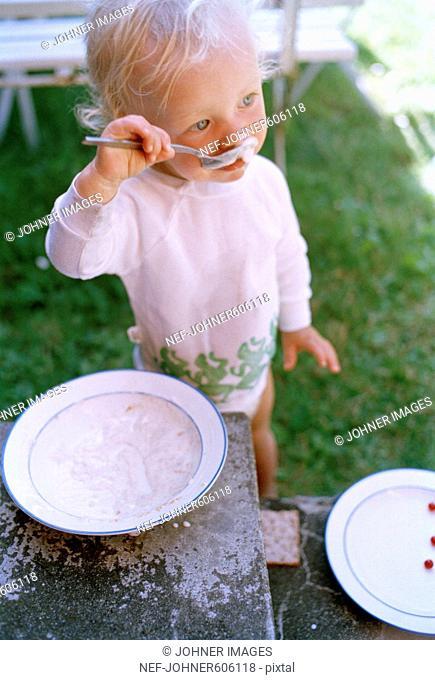 A little child eating youghurt a summerday, Sweden