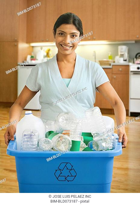 Indian woman carrying bin of recyclable bottles