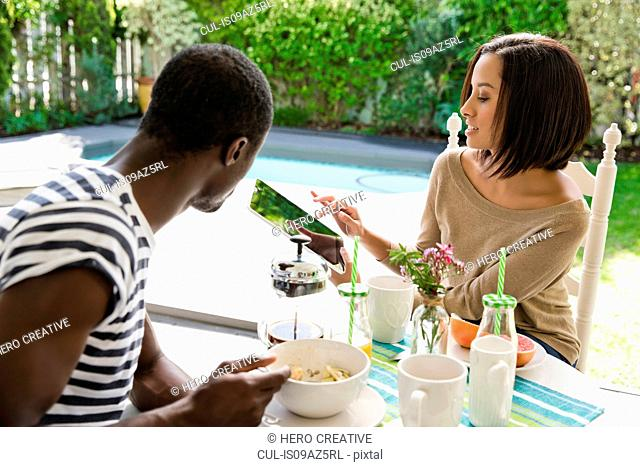 Young couple sharing breakfast using digital tablet