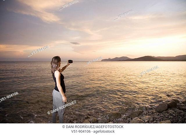 Woman taking a photograph at sunset