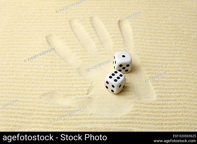 Print of a palm with dices lying on it