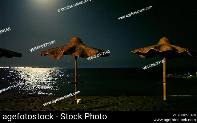 Beach at night in summer with straw umbrellas and moon reflecting in the calm sea